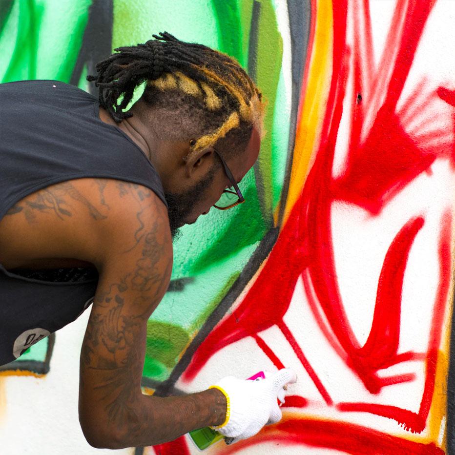 African American artist painting mural.